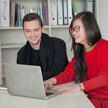 Zwei Studierende am Laptop.